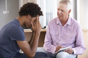 a young man talking to his doctor about mental health treatment